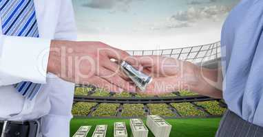 People passing money at football stadium representing corruption