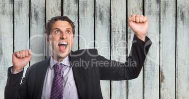 Successful businessman screaming while clenching fists against wooden wall