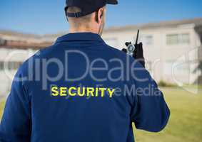 Rear view of security guard using radio against house