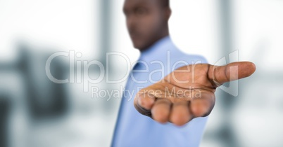 Businessman offering hand over blurred background