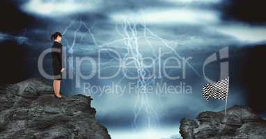Businesswoman and checked flag over rocks against thunderstorm