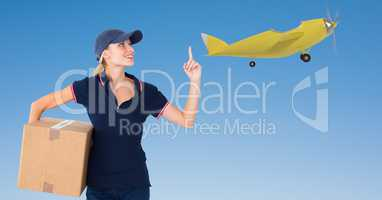 Delivery woman with parcel pointing at airplane