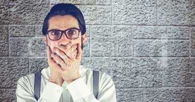 Shocked hipster covering mouth with hands against wall