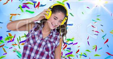 Happy woman listening to music against colorful feathers