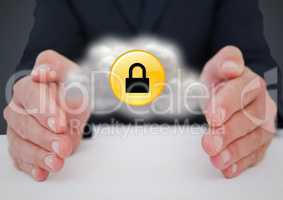 Business man at desk with cloud and yellow lock graphic between hands against grey background