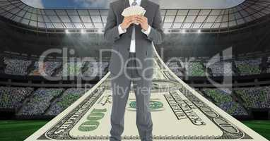 Businessman holding money at football stadium representing corruption