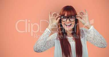 Cheerful redheaded female hipster wearing eyeglasses against orange background