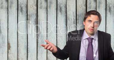 Portrait of confident businessman shrugging shoulders against wooden wall