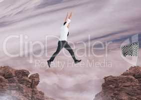 businessman jumping with his hands up to catch the checker flag