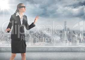 Business woman blindfolded with flare against skyline and grey clouds