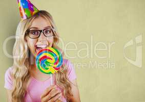 Happy woman wearing party hat while having lollipop