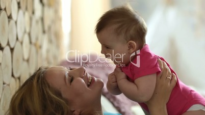 Cheerful mother kissing her adorable baby girl