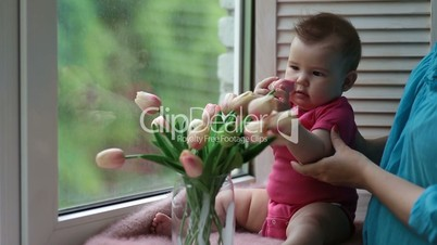 Adorable baby girl playing with tulip flower