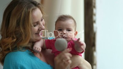 Cute baby and charming mother playing with toy