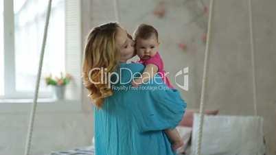 Joyful mother dancing with her baby daughter