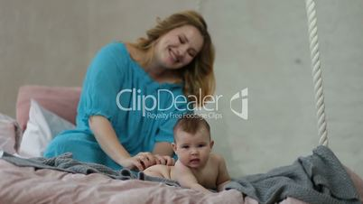Caring young mother massaging naked baby girl