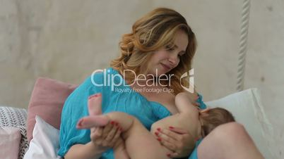 Caring mother breastfeeding her naked baby girl