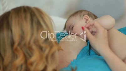 Adorable naked infant child breastfeeding