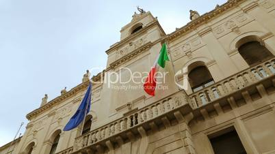 Italian and European flags on the historic building of Town Hall of Padua