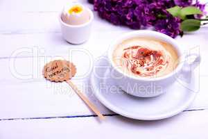 Cup of cappuccino with a saucer on a white wooden background