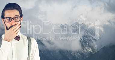 Surprised hipster covering mouth against snow covered mountains