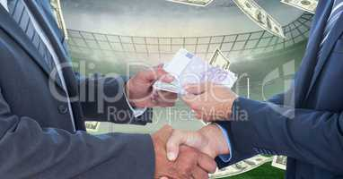 Business people exchanging money at football stadium representing corruption