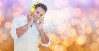 Smiling businessman listening to songs on headphones against bokeh