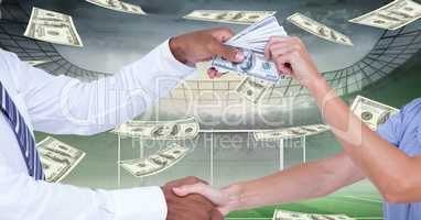 Midsection of people shaking hands while passing money at football stadium representing corruption