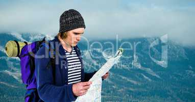 Traveler reading map while carrying backpack on mountain