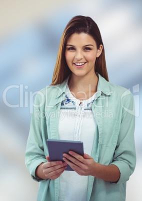 Happy female hipster holding digital tablet against blurred background