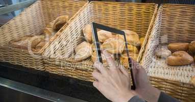 Hands photographing breads on tablet PC at coffee shop