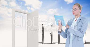 Businesswoman using tablet PC by doors against sky