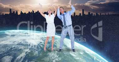 Business people with arms raised on globe
