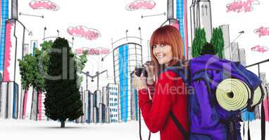 Digitally generated image of female tourist holding camera with buildings and trees in background