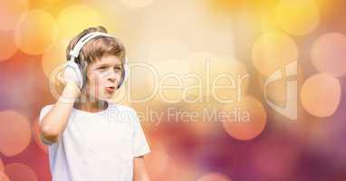 Little boy listening to music on headphones over blur background
