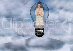 Businesswoman in light bulb surrounded by clouds