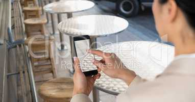Businesswoman taking picture with mobile phone in coffee shop