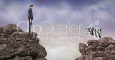 Businessman looking checked flag on rock