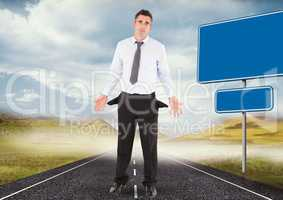 Businessman with empty pockets standing on road by blank signs