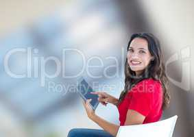 Portrait of smiling woman using digital tablet against blurred background