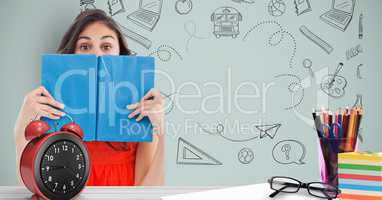 Female student holding book in front of face against graphics
