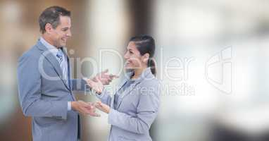 Happy business people talking against blurred background