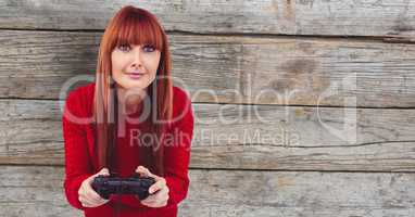 Redhead woman playing video game against wall