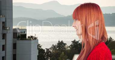 Side view of redhead woman with building and lake in background