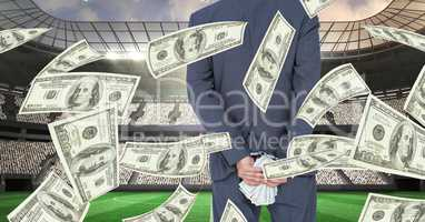 Midsection of businessman holding money behind back at football stadium representing corruption