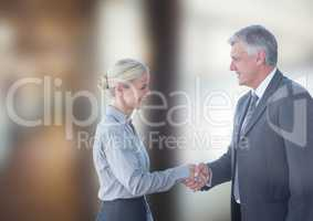 Smiling business people shaking hands against blurred background