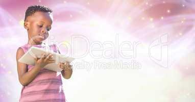 Girl using digital tablet over pink glowing bokeh