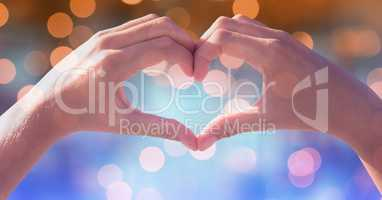 Heart shape made of hands over defocused background