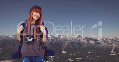Happy female traveler carrying backpack on mountain against clear sky