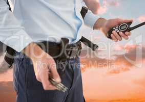Midsection of security guard holding roadio against sky during sunset
